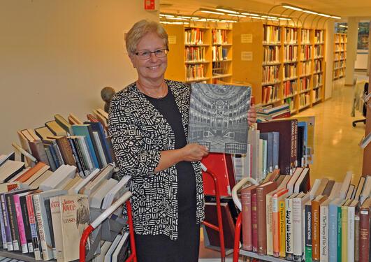 Universitetsbibliotekets Anne Bjørkum Åsmul viser fram en av de flotte bøkene som kan bli din helt gratis.