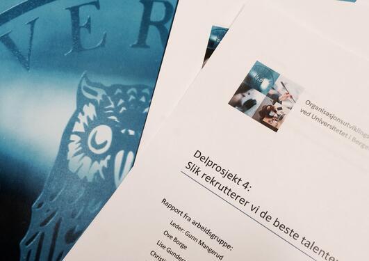 illustrasjonsfoto av rapporter i papirformat med uib logoen som bakgrunn