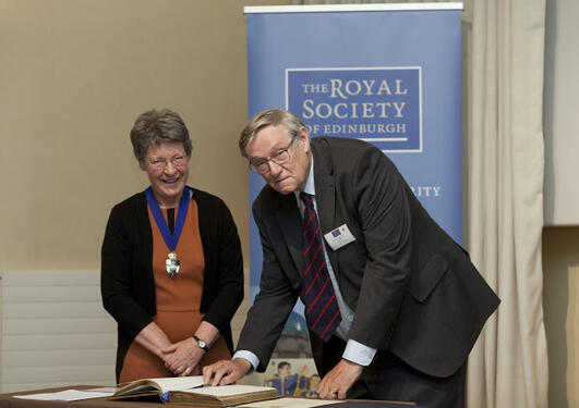 Jocelyn Bell Burnell invites John Birks to sign the Fellows book of the Royal Society of Edinburgh