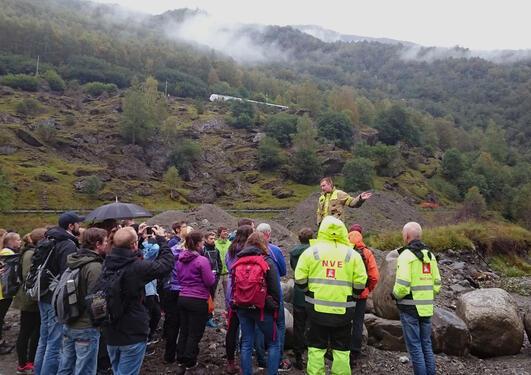 Brannsjef Reinhardt Sørensen illustrerer hvordan Aurland kommune og NVE rekonstruerer Flåmselvens løp i kjølvannet av katastrofeflommen som rammet bygden i oktober i fjor.
