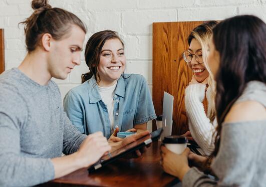 Fire studenter som sitter og diskuterer