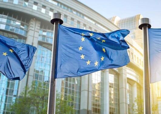 Byggning i Brusse. Tre stk veiend EU_flagg i solen