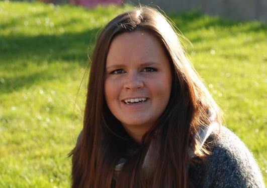 Ung kvinne smiler til kamera, grønt gress i bakgunnen