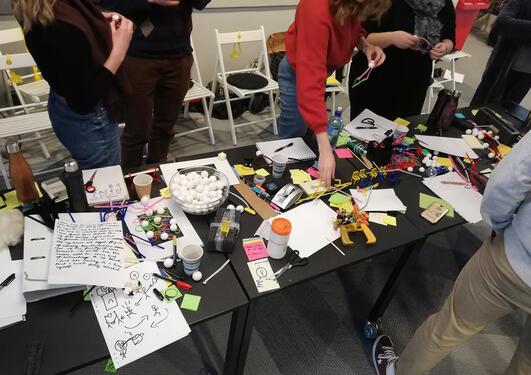Bilde av studenter i kreativ prosess rundt et bord