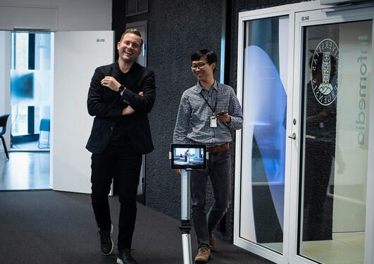 christoff Trattner spaserer i gangen med robot