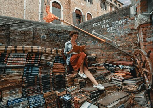 Kvinne sitter i en boktrapp og leser