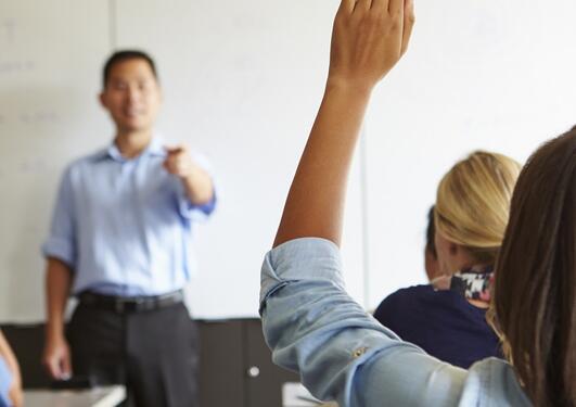 Person som retter opp hånden sett bakfra