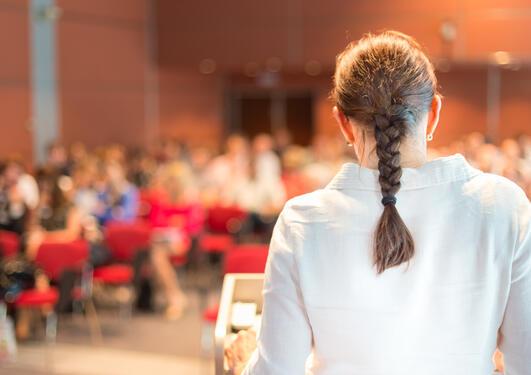 Kvinne står med ryggen mot kamera og snakker til publikum