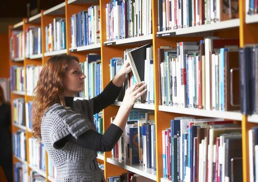 En ung dame tar bøker ut av hylle på et bibliotek