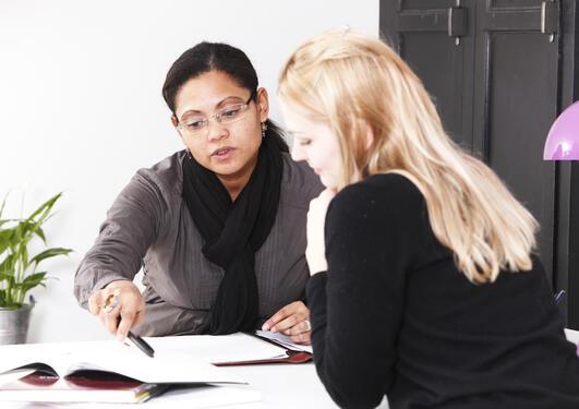 Bildet viser to personer i en samtale.