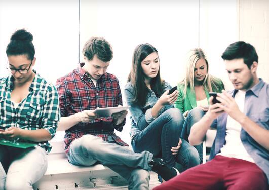 Gruppe unge mennesker med smarttelefon og nettbrett.