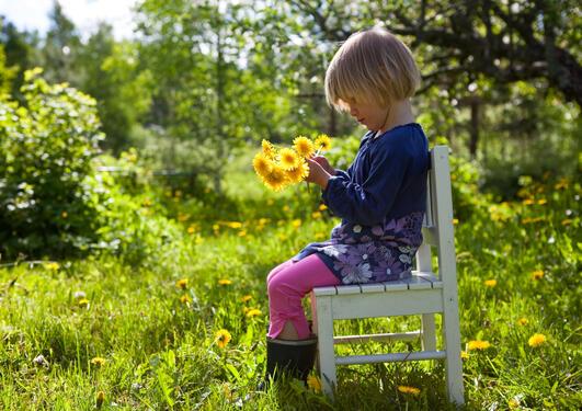Jente på stol i hagen