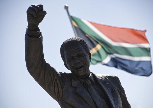 Statue av Nelson Mandela foran det sørafrikanske flagget, brukt for å illlustrere sak om demokrati og grunnlovsfeiring i Sør-Afrika.