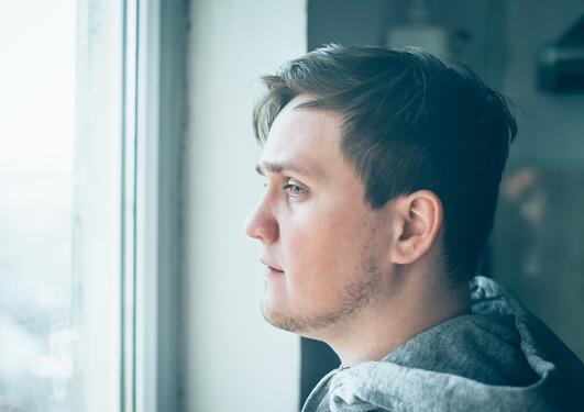 ung mann stirrer ut av vindu