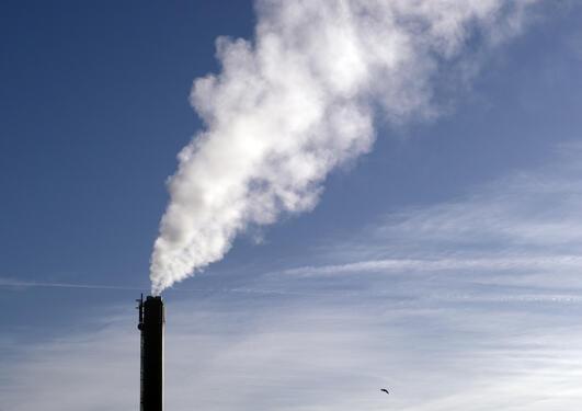 Skorstein og hvit røyk mot blå himmel