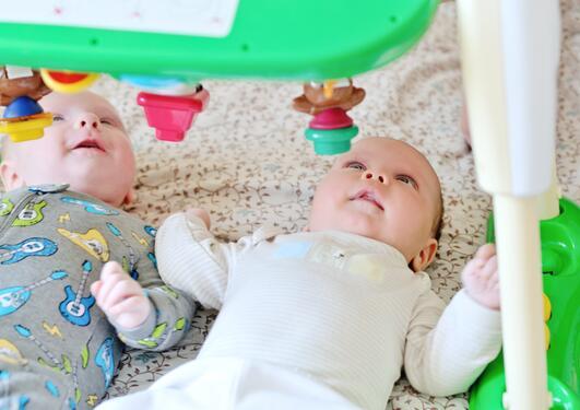 To babyer ligger på lekematte og ser opp på rangle
