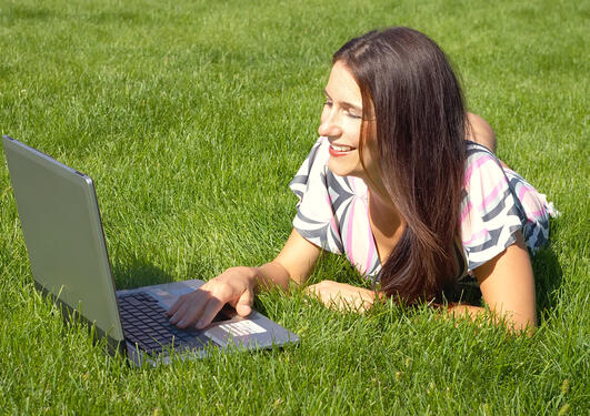 Young beautiful woman, lying on the grass with the laptop