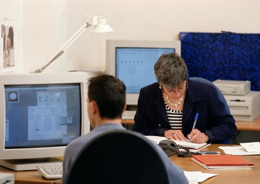 Man og kvinne sitter på kontor og jobber