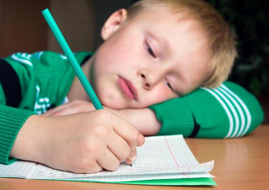 gutt med grønn genser og blondt hår sitter lent over en skoleoppgave. han ser umotivert ut.