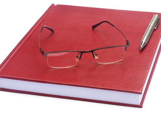 Illustrasjonsbilde rød notatbok med briller og en penn liggende oppå