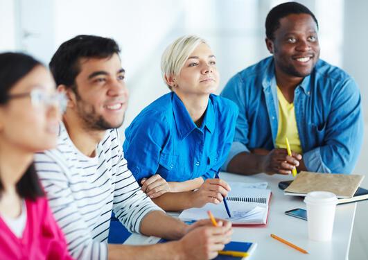 Smilende kolleger rundt et møtebord