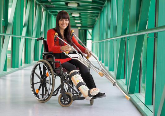 Kvinne i rulllestol og med gips