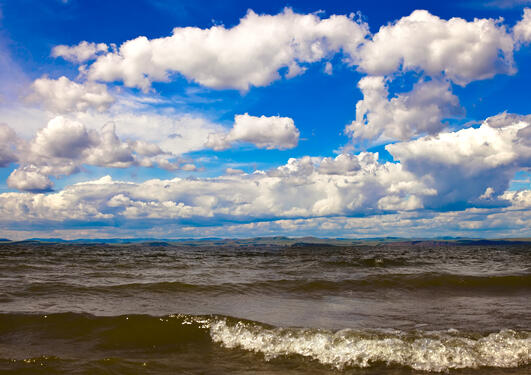 Photo of the ocean with a blue sky with light clouds.