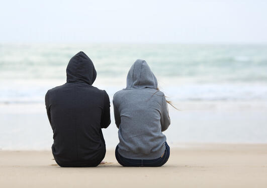 Two youths sitting on a beach