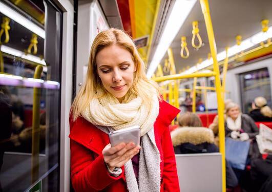 Kvinne leser på mobilen på bussen