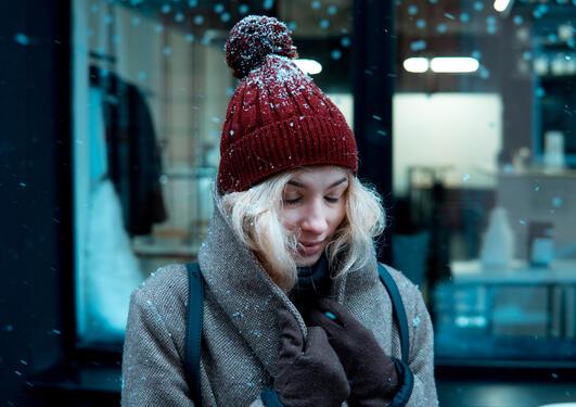 Kvinne står ute med rød topplue, det snør. Hun holder rundt kragen på jakken og drar den tettere rundt seg, blondt hår, øynene lukket. I et bymiljø
