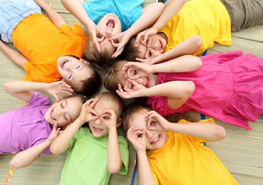 Sju barn med fargerike klær ligger med hodene mot hverandre