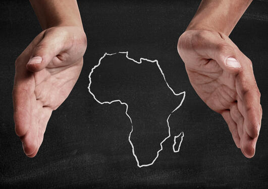 Illustration photo showing two hands cupping an outlined map of the African continent.