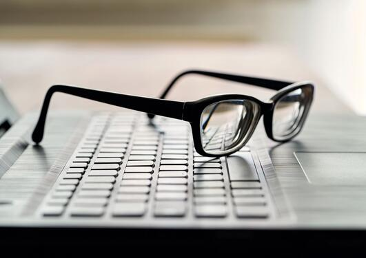 The picture shows  glasses and computer keyboard