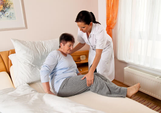Sykepleier som hjelper pasient opp i sengen