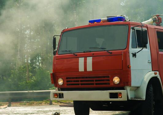 Bilde av en brannbil med røyk i bakgrunnen