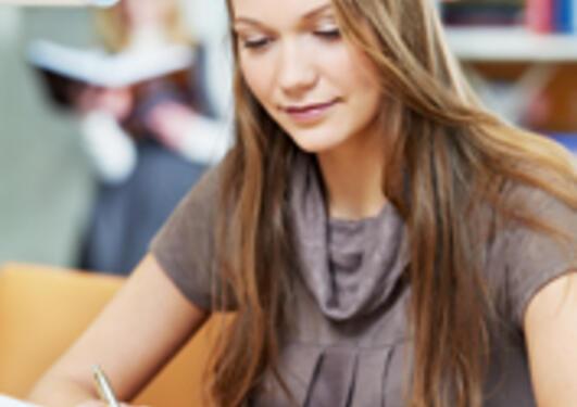 Jente studerer på bibliotek