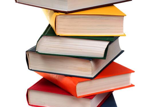 Bildet viser en stabel med fargerike bøker