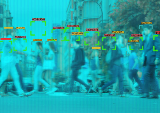 Blurry blue image showing a crowd of people with green boxes superimposed on the image, suggesting some kind of machine vision.
