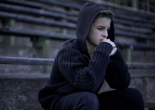 En ung gutt sitter med hettegenser på en trapp. Han ser betenkt og bekymret ut