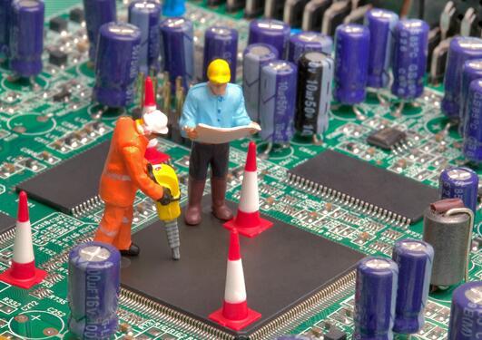 Mini workmen repairing a broken circuitboard