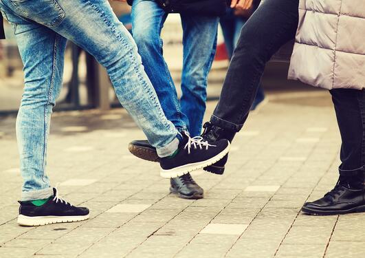 Folk som hilser med skoene (corona-hilsen)