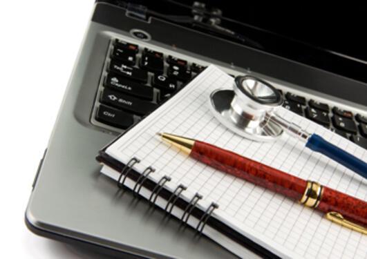 Notatblokk, penn og stetoskop ligg på tastaturet til ein laptop