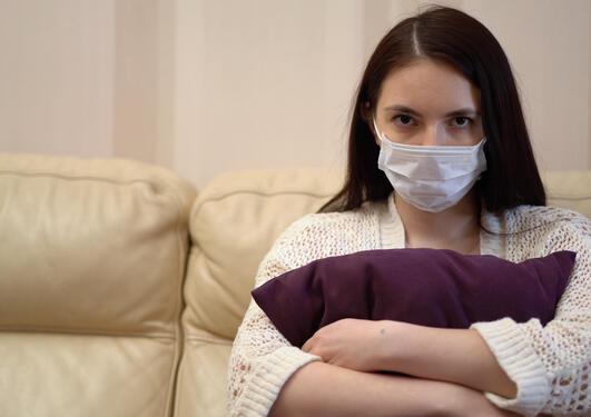 Jente sitter trist i sofa, holder på en pute og har ansiktsmaske på seg