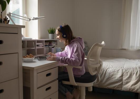 jente sitter foran pcen på rommet sitt