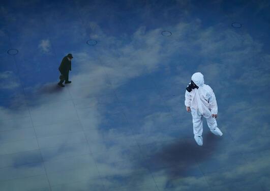 Illustrasjonsbilde. Mann med smittevernutstyr står på en opprutet blå flate og ser bort på en mann i jakke.