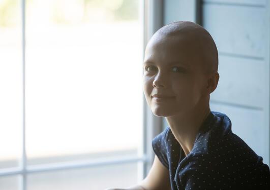 Kvinne uten hår grunnet kreftbehandling sitter ved vinduet, ser i kameraet og smiler