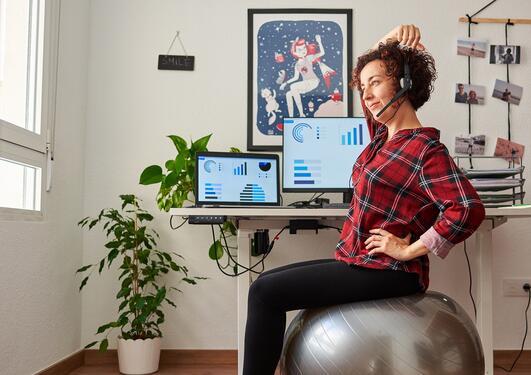 Kvinne sitter på sitteball ved et hev-senk skrivebord, med headset, mens hun klør seg i hodet.