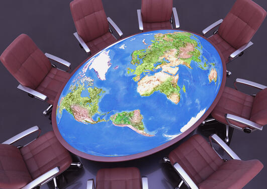 Stock photo of conference table of the world surrounded by chairs.