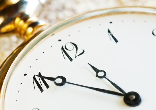 Deler av en urskive som viser 11:55.