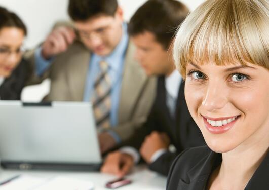 Bildet viser en smilende karrierekvinne.